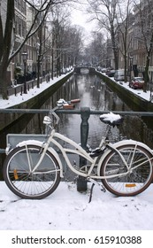 White bike with brown wheels in snow in winter near the canal in Amsterdam
