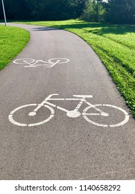 White bike path sign painted on an asphalt road.