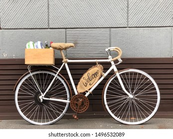 """White bike with the words """"Welcome."""" Scenery at the entrance to the store, near the wall a sports bike with the inscription, cheese and wine in the trunk."""