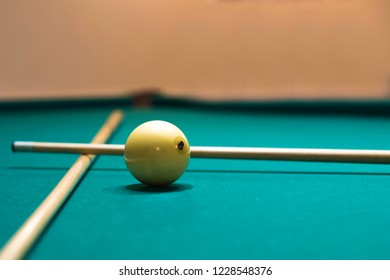 White billiard ball numbered 8 ,  two cues on the surface of  green pool table. Focus on billiard ball. Russian billiard.