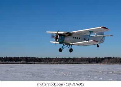 A white biplane is over the snowy land.