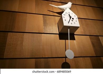 White bird clock on wooden wall