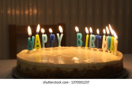 White birthday cake with colorful happy birthday letters