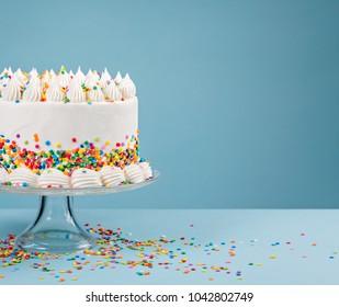White Birthday cake with colorful Sprinkles over a blue background.