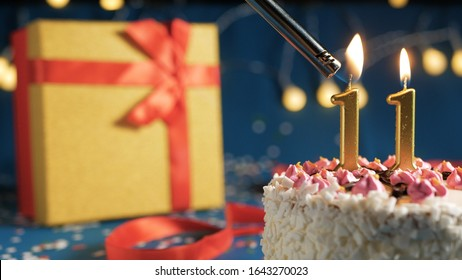 White birthday cake number 11 golden candles burning by lighter, blue background with lights and gift yellow box tied up with red ribbon. Close-up view
