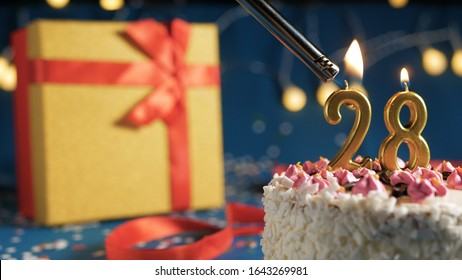 White birthday cake number 28 golden candles burning by lighter, blue background with lights and gift yellow box tied up with red ribbon. Close-up view