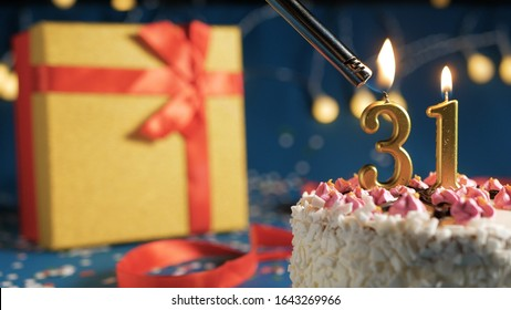 White birthday cake number 31 golden candles burning by lighter, blue background with lights and gift yellow box tied up with red ribbon. Close-up view