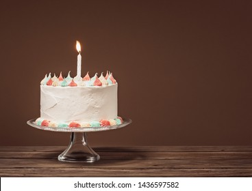 White Birthday cake with pastel colored icing and lit candle on a wooden table