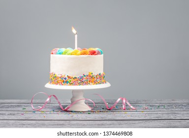 White Birthday cake with rainbow icing, colorful Sprinkles and one candle over a gray background.