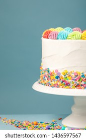 White Birthday cake with rainbow icing and colorful Sprinkles over a blue background.