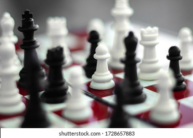 White and black chess in a chaotic arrangement, on a red-white chessboard on a stone background