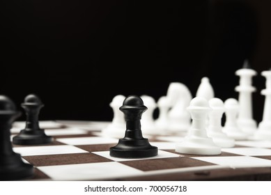 White and black chess pieces on a blackboard
