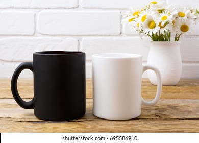 White and black coffee mug mockup with white field chamomile bouquet in handmade rustic vase.  Empty mug mock up for design promotion.