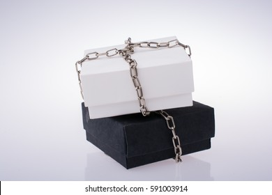 White and black gift boxes with chains on a white background