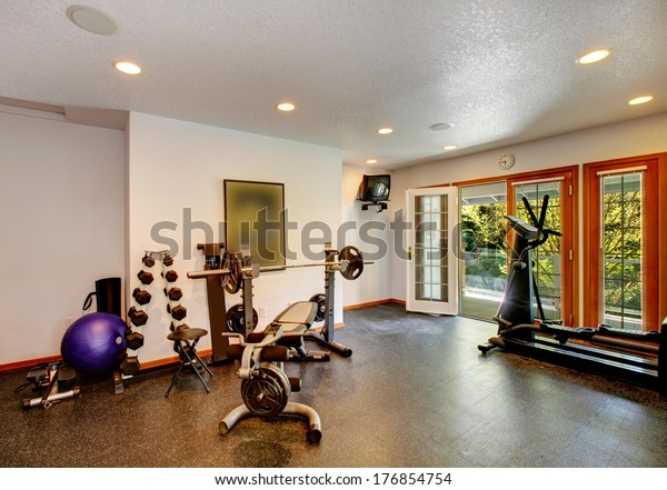 White and black home gym with different exercise equipments and tv