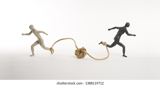 White and black men run with a rope tied to the foot. Concept of the absurd competition. Isolated on white background. With space copy text. Shooting in studio.