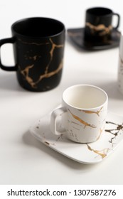 White and black mugs with a saucer. Cups for coffee and tea on a white background. Utensils for any holiday, luxury wedding, birthday or party. Style Japanese art of repair broken dishes, kintsugi.