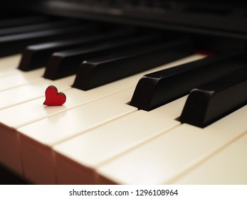 White black piano with red heart, love to music