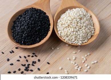 White and black sesame seeds in a wooden spoon