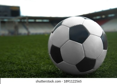 white and black soccer ball on green grass and stadium background. sports betting idea