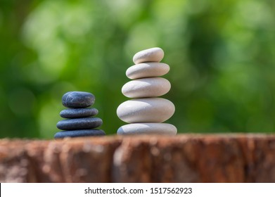 White and black stones cairns in daylight, poise light pebbles on wooden stump in front of green natural background, zen like sculpture, simplicity, harmony and balance