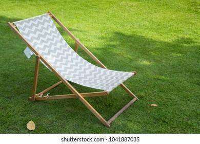 white and black striped deckchair on green grass in garden