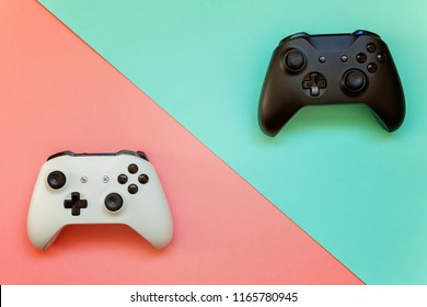 White and black two joystick gamepad, game console on pink and blue colourful trendy modern fashion pin-up background. Computer gaming competition videogame control confrontation concept
