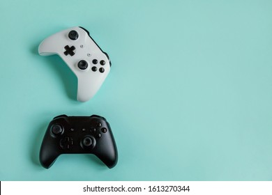 White and black two joystick gamepad, game console isolated on pastel blue colourful trendy background. Computer gaming competition videogame control confrontation concept. Cyberspace symbol