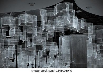 White and black unusual textures. Abstract background of curved striped transparent hangings under ceiling. Futuristic interior decorations. White circle shaped lamps. Geometric backdrop.
