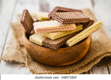 White and black wafer biscuits in wooden bowl on linen