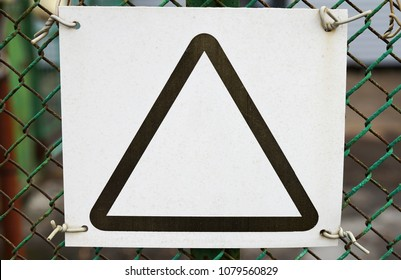 A white blank with a black triangle on a mesh fence, a paper sheet is screwed with a wire.