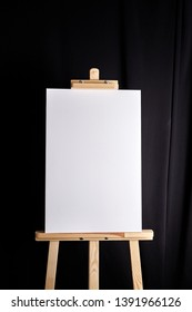 White blank canvas stands on a wooden artistic easel on black curtain background. Vertical rectangular mockup canvas wrapped on stretcher bar, front view