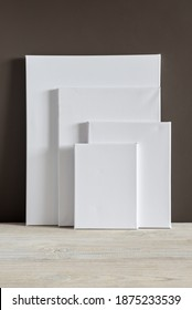 White blank canvases of various sizes stand against a dark wall. Mockup. Materials for painting with oil paints and acrylics. Close-up photo.