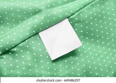 White blank clothes label on green silk as a background