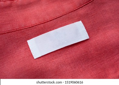 White blank clothing tag label on red linen shirt fabric texture background