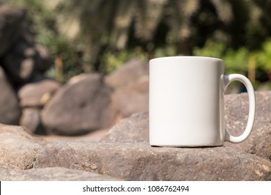 White blank coffee mug mock up, close-up of mug outside in the sunshine on some large decorative garden stones.Perfect for businesses selling mugs, just overlay your quote or design on to the image.