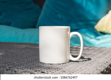 White blank coffee mug mock up set outside on a rattan table with cushions in the background. Perfect for businesses selling mugs, just overlay your quote or design on to the image.