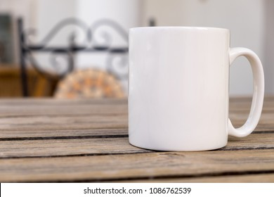 White blank coffee mug mock set-up, outside on a little wooden table with an ironwork chair in the background.Perfect for businesses selling mugs, just overlay your quote or design on to the image.