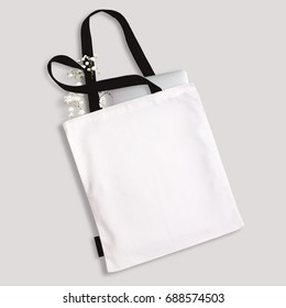 White blank cotton eco tote bag with black straps, handles and little label, laptop and flowers inside. Design mockup.