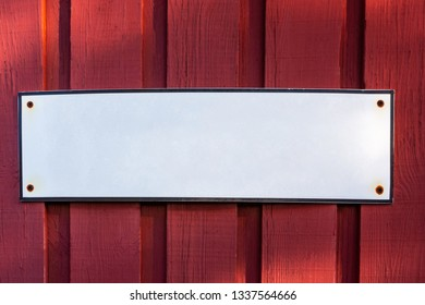 A white blank empty steel sign with copyspace on a red wooden barn wall.