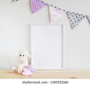 White blank frame mockup for text, photo, art, lettering on wooden table with girl room decorations. Nursery decor.