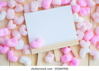 White blank frame surrounded with pink hearts in blur sweet tone, flat lay.