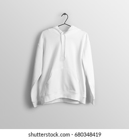 White blank hoodie mockup on hanger, hanging against empty wall background.