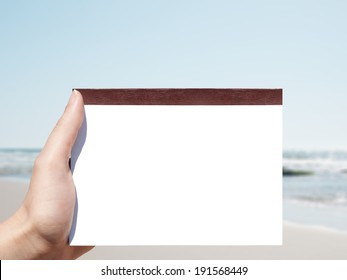 white blank horizontal notebook in woman hand and beach background