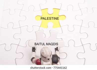 White blank jigsaw puzzle with missing pieces written with text Baitul Maqdis and Palestine.