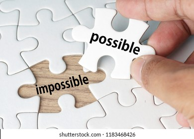 White Blank jigsaw puzzle with wording possible and missing area with wording impossible. motivational concept