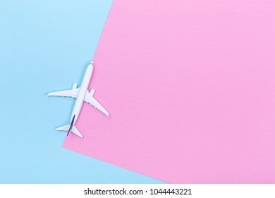 White blank model of passenger airplane on pastel colored paper texture, flat lay