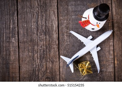White blank model of passenger plane and snowman on rustic wooden background. Christmas and new Year celebration