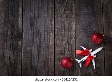 White blank model of passenger plane and christmas decoration toys on rustic wooden background. New Year celebration