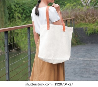 white blank nature canvas tote bag with leather strap mock up in woman hand